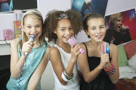Pre teen : Girls using brushes microphones to sing at a slumber party