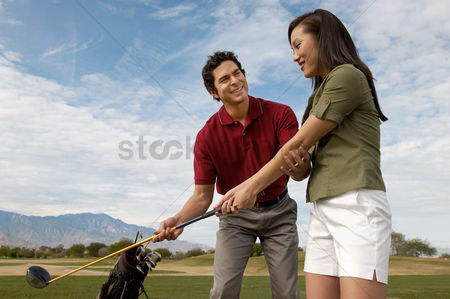 Teacher : Golf coach assisting mid-adult woman with swing