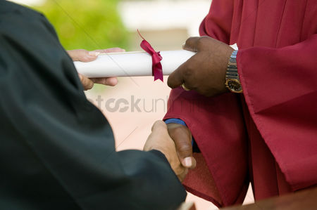 University : Graduate receiving diploma and handshake mid section