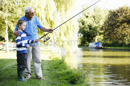 Mature : Grandfather and grandson fishing together