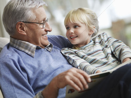 Retirement : Grandfather reading to girl  3-4  close-up