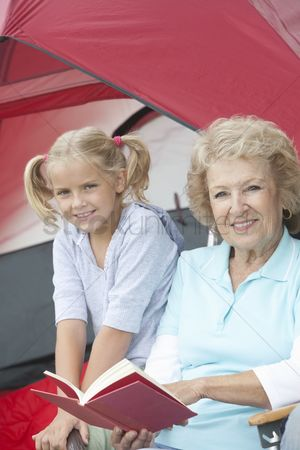 Pitch : Grandmother sits reading a book with her grand-daughter outside a tent