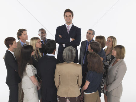 Leadership : Group of businesspeople staring at tall man