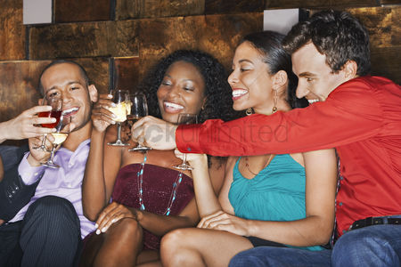 Appearance : Group of friends toasting sitting in bar