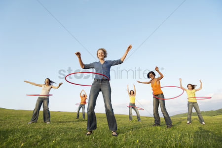 Grass : Group of friends using hula hoops in mountain field low angle view