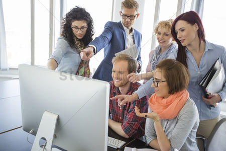 30s adult : Group of smiling businesspeople using computer together in office