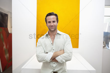 Interior background : Half-length portrait of smiling young man in front of yellow painting