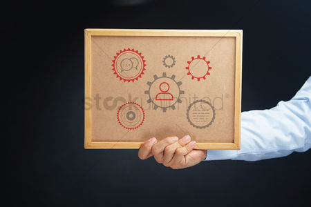 Cork board : Hand holding a board with cogwheels concept