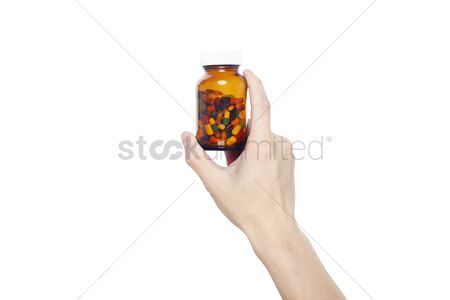 Medication : Hand holding a bottle of pills
