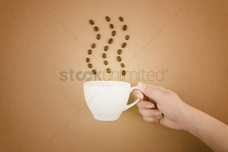 Strong : Hand holding a coffee cup with coffee beans concept