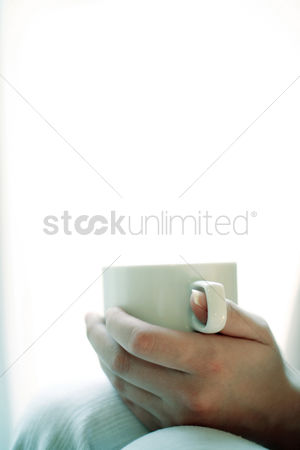 Sitting on lap : Hand holding a cup of coffee
