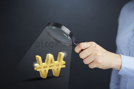 South korea : Hand holding magnifying glass with won currency symbol