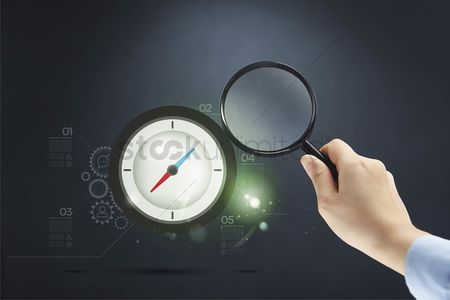 Magnifying glass : Hand pointing magnifying glass towards compass