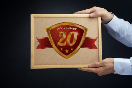 Cork board : Hands holding a board with anniversary 20 label