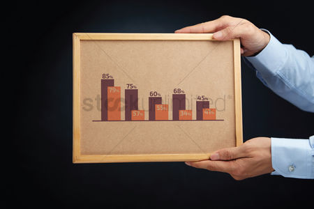 Cork board : Hands holding a board with double bar graphs