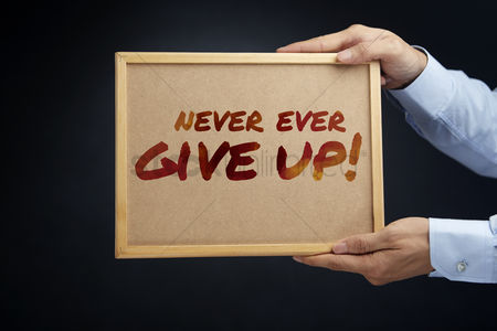 Cork board : Hands holding a board with the text never ever give up