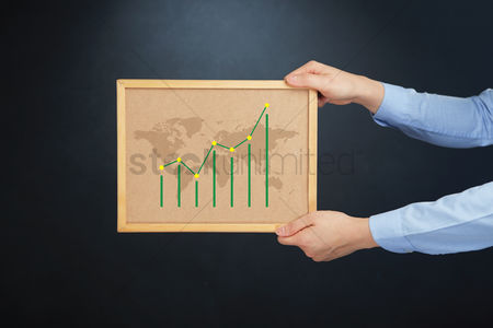 Cork board : Hands holding board with bar charts and map
