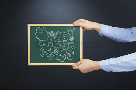 Client : Hands holding chalkboard with business plan concept