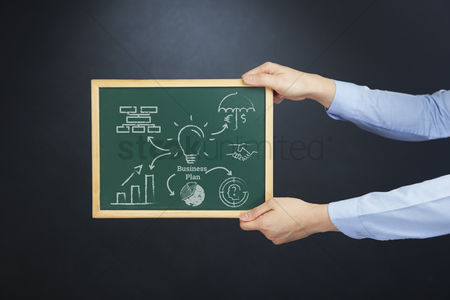 Handdrawn : Hands holding chalkboard with business plan concept