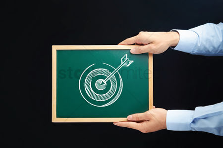 Handdrawn : Hands holding chalkboard with business target concept