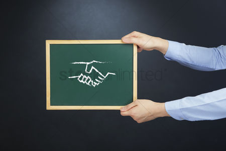 Handdrawn : Hands holding chalkboard with handshake drawing