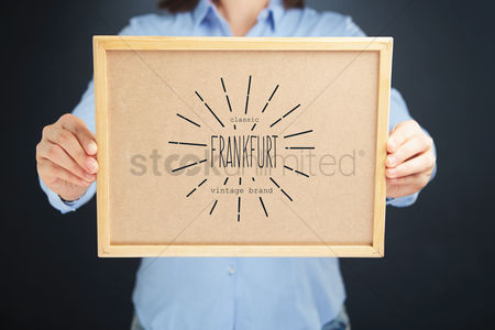 Cork board : Hands holding cork board with frankfurt trademark concept
