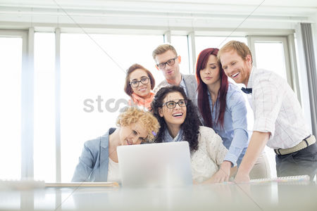 People : Happy business colleagues with laptop discussing in creative office