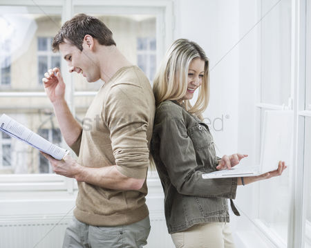 Czech republic : Happy business couple holding book and laptop in office