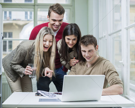 Internet : Happy business people using laptop in meeting