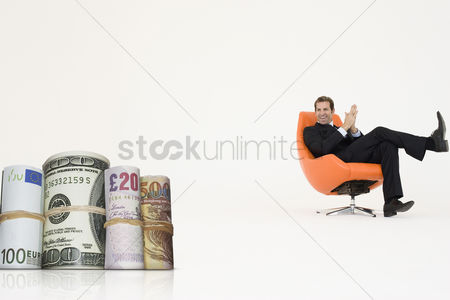 British ethnicity : Happy businessman looking at money rolls representing growth in international business