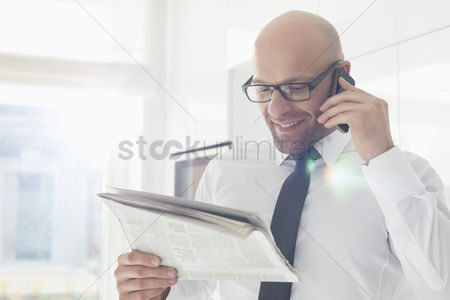 Bald : Happy businessman on call while reading newspaper at home