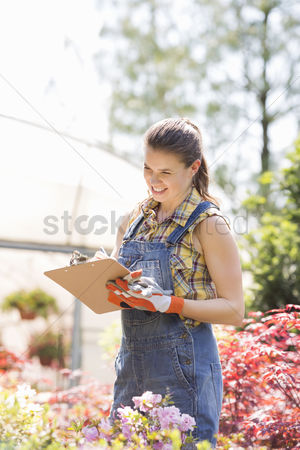 Greenhouse : Happy female supervisor writing on clipboard outside greenhouse