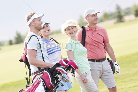 40 44 years : Happy friends walking at golf course