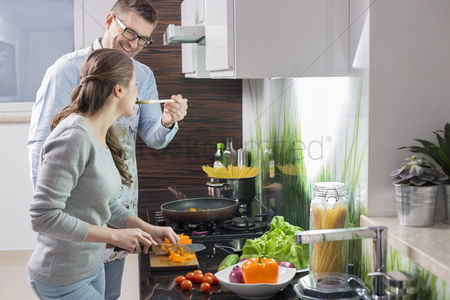 Three quarter length : Happy man feeding food to woman cutting vegetables in kitchen