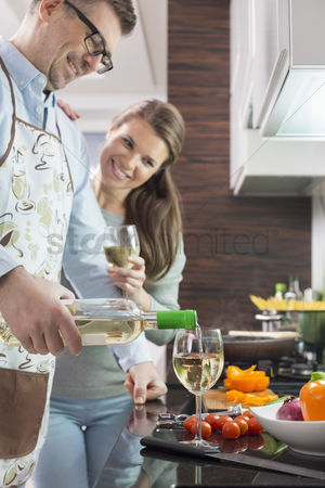 Wine bottle : Happy man pouring white wine in glass while cooking with woman at kitchen