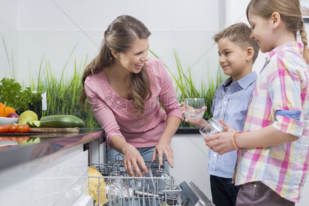 Pre teen : Happy mother and children placing glasses in dishwasher