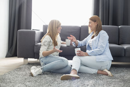 Daughter : Happy mother and daughter talking while having coffee in living room