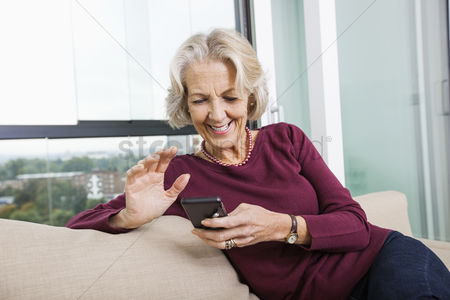 Senior women : Happy senior woman text messaging through smart phone on sofa at home