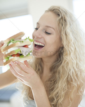 Czech republic : Happy woman eating large sandwich in house