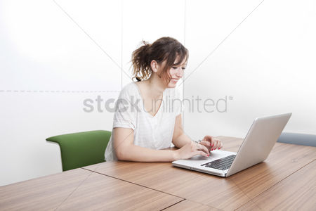 Technology : Happy young businesswoman using laptop at table