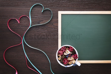 Conceptual : Heart shaped ribbon with dried flowers and blackboard