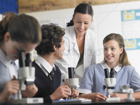 Teacher : High school students talking with teacher in chemistry class