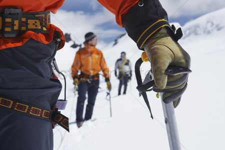 Jacket : Hikers using walking sticks in snowy mountains mid section on front man