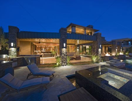 Outdoor : House exterior lit up at night  with patio furniture