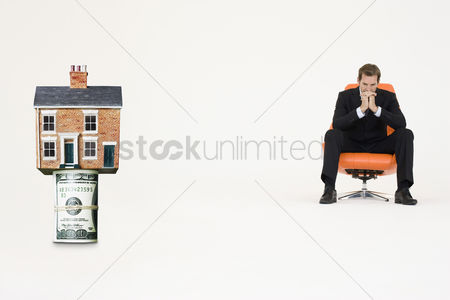 Contemplation : House on top of roll of bills with pensive businessman on chair representing expensive real estate