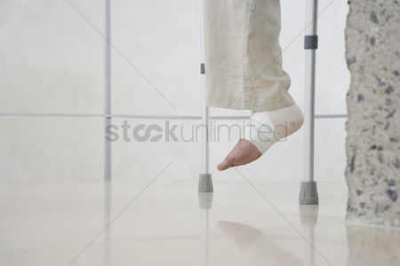 First : Human foot of person on crutches low section