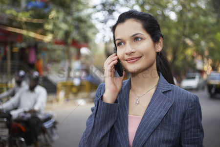 Cell phone : India business woman using mobile phone on street