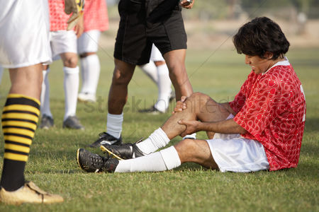 Pitch : Injured soccer player sitting on pitch portrait