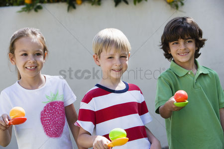 Posed : Kids holding eggs in spoons for egg race