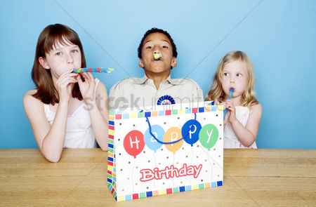Celebrating : Kids playing with party blowers